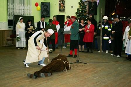 """Fot. 6) Masarz przystępuje do zebrania """"krwi"""" misia i rozdzielenia jej pośród uczestników zabawy."""